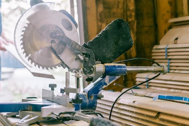 Professionele verstekzaag die op een stapel planken staat met trimplanken voor huisbekleding, constructie en reparatieconcept
