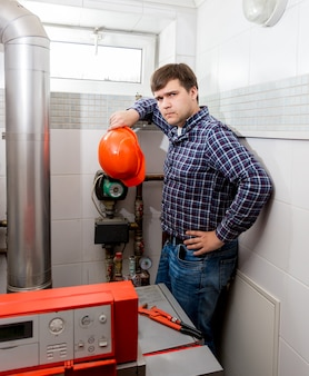 Professionele verwarde loodgieter die ingewikkeld verwarmingssysteem bekijkt