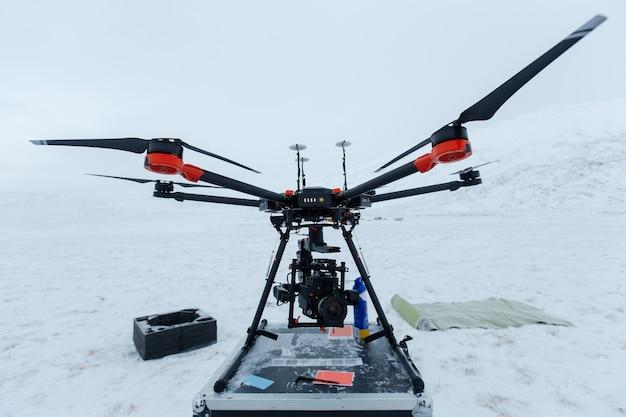 Professionele videocamera en moderne drone in koude winterveld