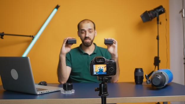 Professionele videograaf die oplaadbare batterijen vasthoudt en opneemt. elektronica en camera-apparatuur van het type np-f, uitrusting voor videografie, maker van sociale media voor online distributie