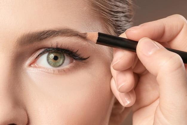 Professionele visage kunstenaar make-up toe te passen op het gezicht van de vrouw, close-up