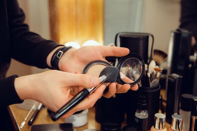 Professionele visagist die bij salon werkt. de man in het vrouwelijk beroep. gendergelijkheid concept. mannelijke handen met borstelclose-up