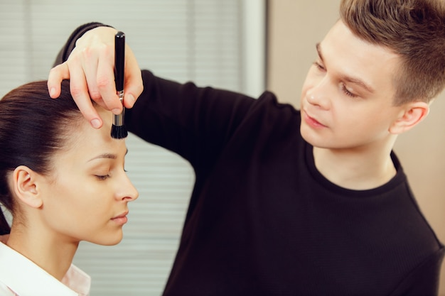 Professionele visagist die met mooie jonge vrouw werkt. de man in het vrouwelijk beroep. gendergelijkheid concept