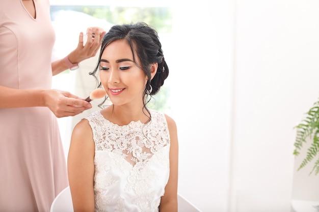 Professionele visagist die thuis met jonge aziatische bruid werkt