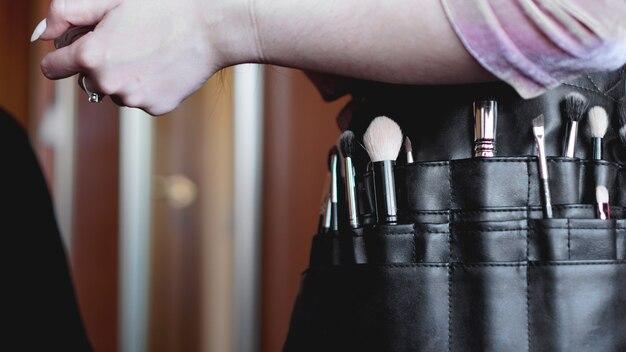Professionele visagist met een heuptasje met kwastjes. make-up kwasten en hand