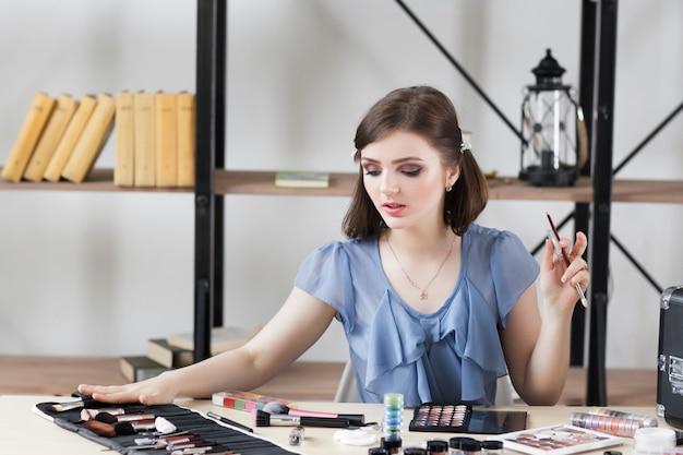 Professionele visagiste die borstel voor make-up kiest