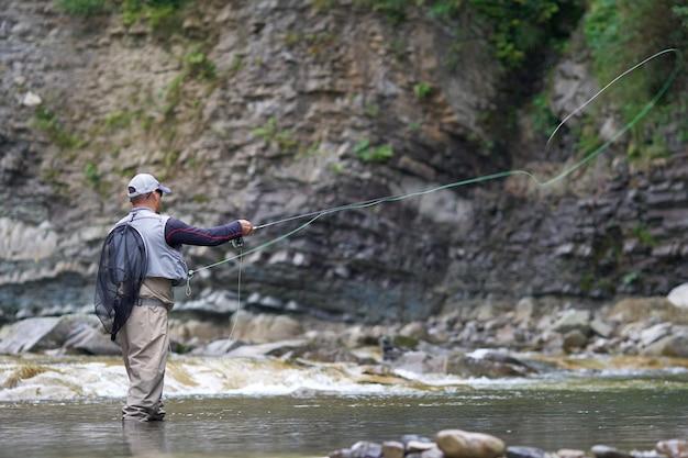 Professionele visser in waterdichte outfit hengel gooien in ruige rivier tussen bergen. mooie zomerse natuur rondom. concept van visserij.