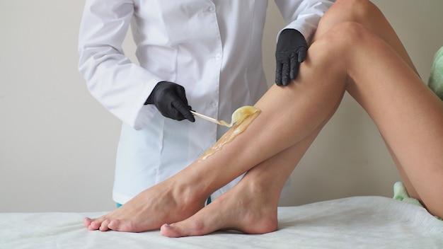Professionele voet waxen close-up. vrouw op de bank, voorbereiden op ontharing. het concept van ontharing