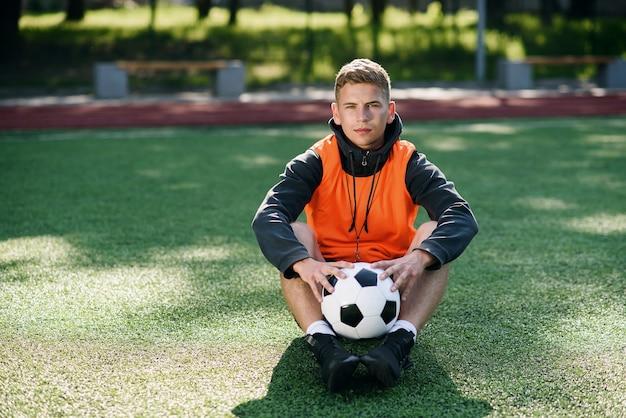 Professionele voetbalcoach in een oranje vest en een fluitje op de nek.