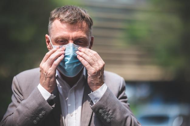 Professionele volwassen zakenman die chirurgisch gezichtsmasker draagt ter bescherming van coronavirus covid-19, bedrijfsmedewerker nieuwe normale levensstijl op de achtergrond van stedelijke stadswolkenkrabber, persoon in pak