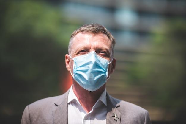 Professionele volwassen zakenman die chirurgisch gezichtsmasker draagt ter bescherming van coronavirus covid-19