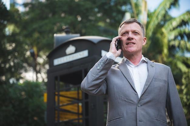 Professionele volwassen zakenman praten met smartphone, gesprek werken met slim apparaat in marketing communicatiepartner teamwerk, slimme mensen in stedelijke stad levensstijl, ceo-manager in pak