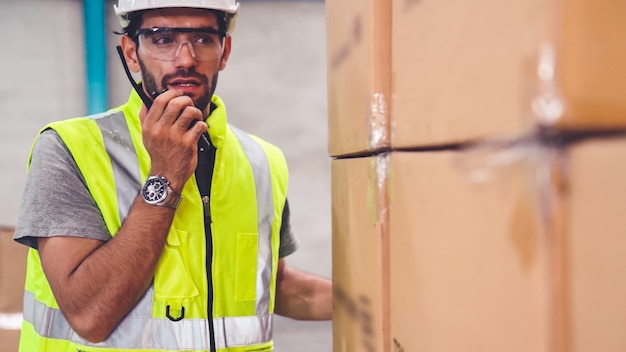Professionele vrachtarbeider praat op draagbare radio om contact op te nemen met een andere werknemer