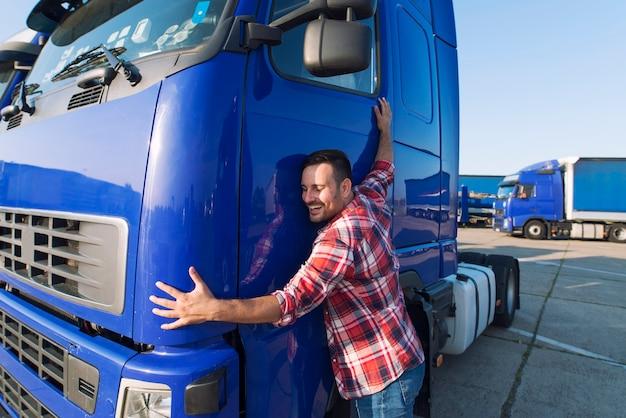 Professionele vrachtwagenchauffeur die zijn vrachtwagencabine knuffelt die van zijn baan houdt