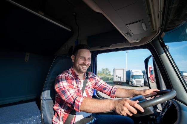 Professionele vrachtwagenchauffeur in vrijetijdskleding die veiligheidsgordel draagt en zijn vrachtwagen naar bestemming rijdt