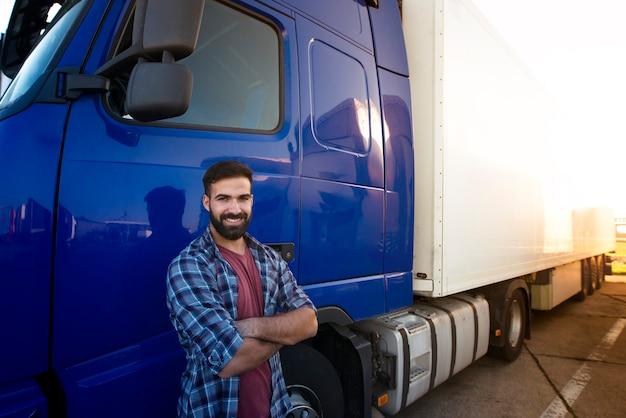 Professionele vrachtwagenchauffeur met gekruiste armen die zich bij zijn semi vrachtwagenvoertuig bevinden.