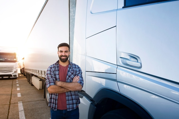 Professionele vrachtwagenchauffeur met gekruiste armen permanent door semi vrachtwagenvoertuig.