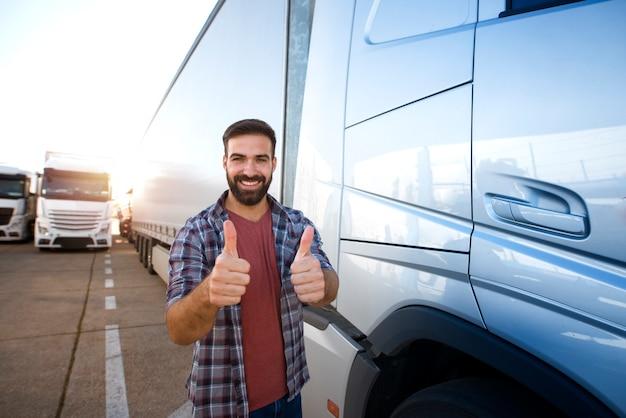 Professionele vrachtwagenchauffeur van middelbare leeftijd die duimen omhoog houdt en zich door zijn vrachtwagen bevindt.