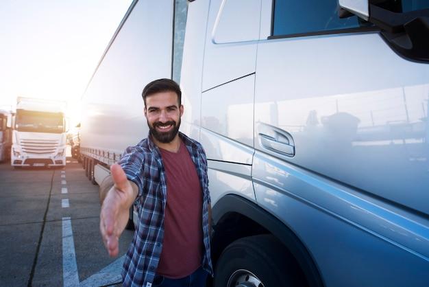 Professionele vrachtwagenchauffeur van middelbare leeftijd die voor zijn vrachtwagen staat en schudt aan nieuwe rekruten.