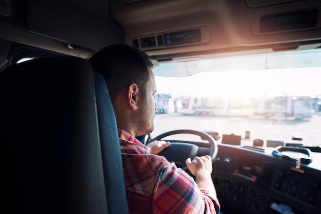 Professionele vrachtwagenchauffeur van middelbare leeftijd in vrijetijdskleding die vrachtwagenvoertuig bestuurt voor een lange transportroute die goederen op de markt levert.
