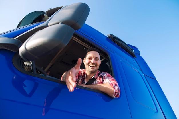 Professionele vrachtwagenchauffeur van middelbare leeftijd zitten in de cabine van zijn voertuig en schuddende hand geven aan nieuwe rekruten.