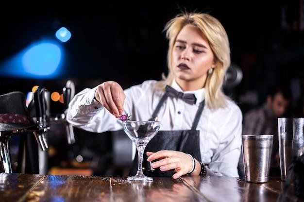 Professionele vrouw barman formuleert een cocktail in de nachtclub