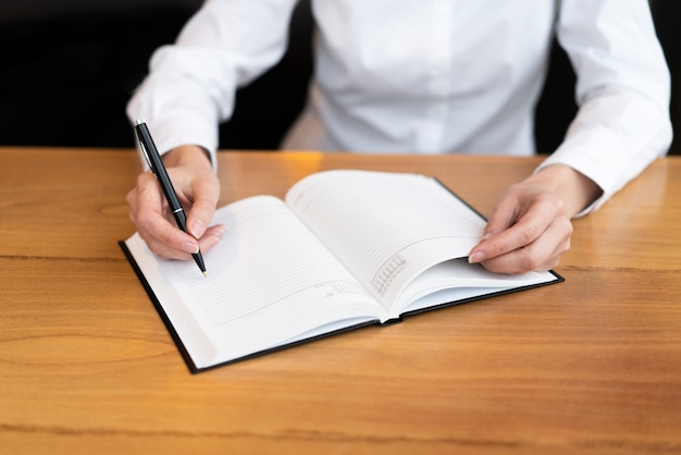 Professionele vrouw die in agenda schrijft