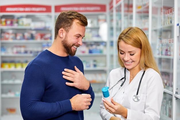 Professionele vrouwelijke apotheker die mannelijke custome helpt