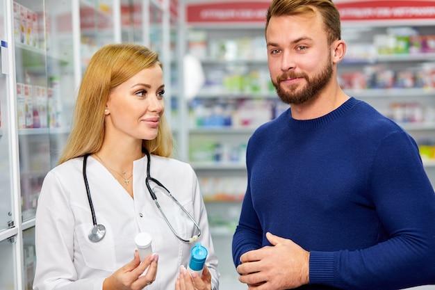 Professionele vrouwelijke apotheker die mannelijke klant helpt
