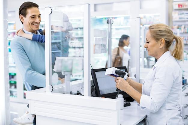 Professionele vrouwelijke apotheker verkoop van medicatie en man met meisje