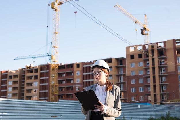Professionele vrouwelijke architectuur die op klembord bij bouwwerf schrijft