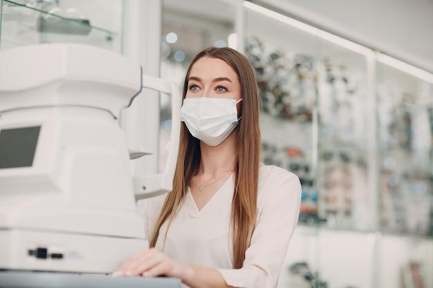 Professionele vrouwelijke arts die oogtesten met elektronische digitale moderne apparatuur gebruikt om de visie te controleren.