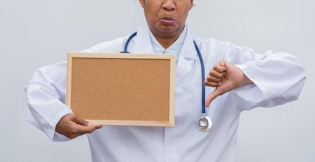 Professionele vrouwelijke arts in witte jas over witte geïsoleerde en witte leeg bord en duimen naar beneden.