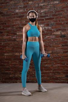Professionele vrouwelijke atleet training op bakstenen muur achtergrond met gezichtsmasker.