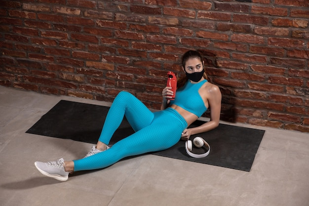 Professionele vrouwelijke atleet training op bakstenen muur achtergrond met gezichtsmasker