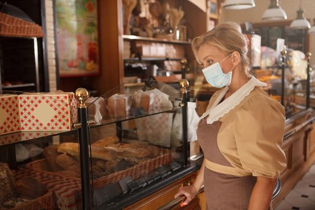 Professionele vrouwelijke bakker die in haar broodwinkel werkt en een medisch gezichtsmasker draagt tijdens de pandemie van het coronavirus