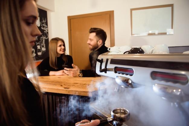 Professionele vrouwelijke barista die de koffiemachine met behulp van.