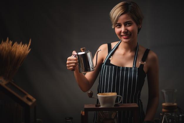 Professionele vrouwelijke barista glimlachen, portret van jonge vrouwelijke koffiezetapparaat in het café