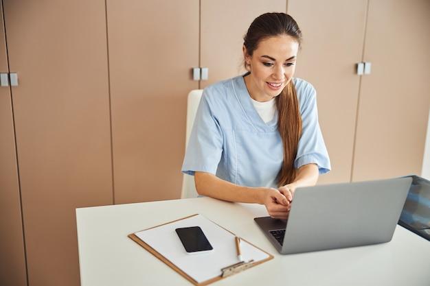 Professionele vrouwelijke dokter die aan haar laptop werkt