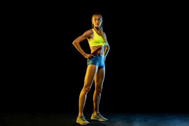 Professionele vrouwelijke estafette racer training op zwarte studio