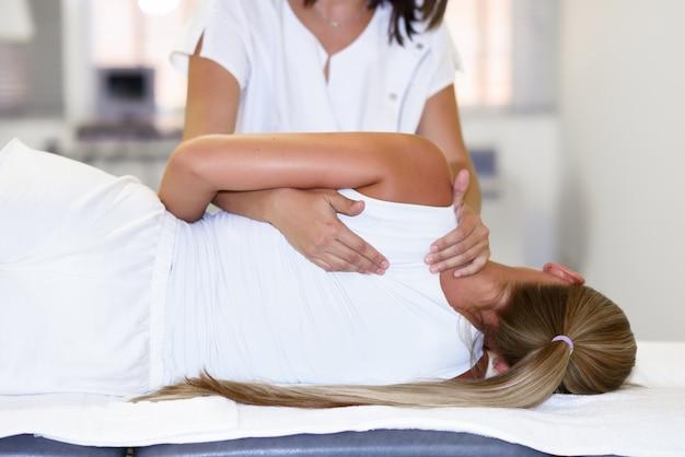 Professionele vrouwelijke fysiotherapeut die schoudermassage geeft aan blonde vrouw