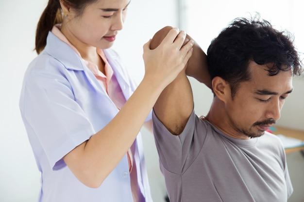 Professionele vrouwelijke fysiotherapeut die schoudermassage geeft aan de mens.