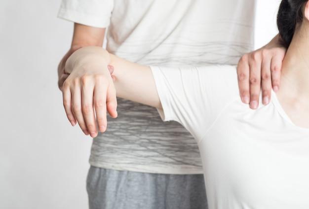 Professionele vrouwelijke fysiotherapeut die schoudermassage geven aan de mens in het ziekenhuis