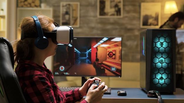 Professionele vrouwelijke gamer die vr-headset en draadloze controller gebruikt om computergames te spelen. man sms't op de telefoon op de achtergrond.