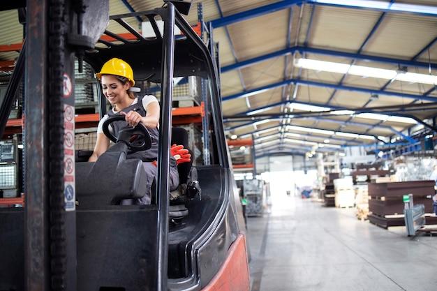 Professionele vrouwelijke industriële chauffeur heftruck machine in het magazijn van de fabriek