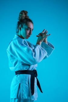 Professionele vrouwelijke judoist in witte judo kimono oefenen en trainen geïsoleerd op blauwe neoned studio achtergrond.