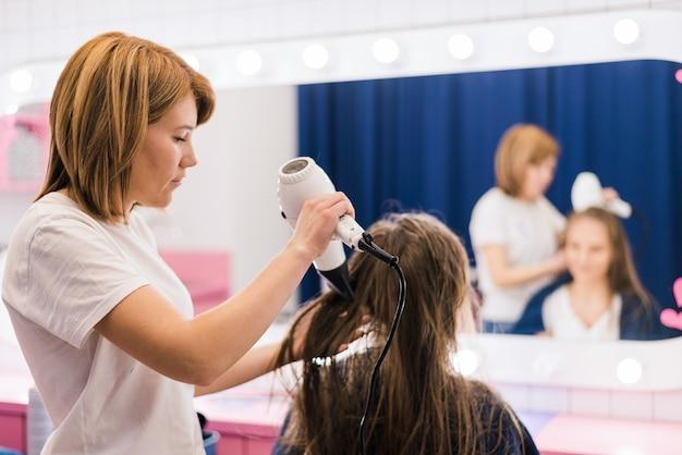Professionele vrouwelijke kapper drogen vrouw haarstyling met behulp van föhn in de salon van de kapsalon