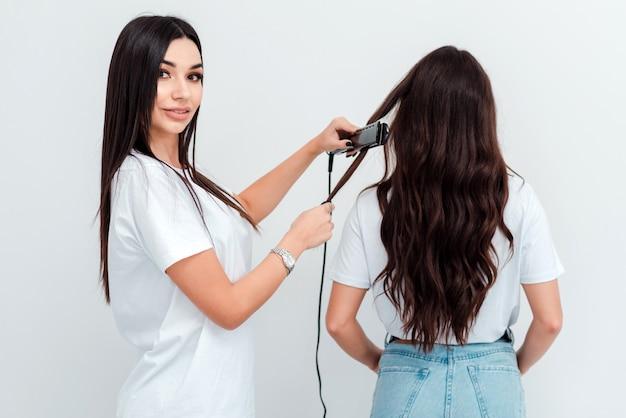 Professionele vrouwelijke kapper maakt het kapsel van de vrouw