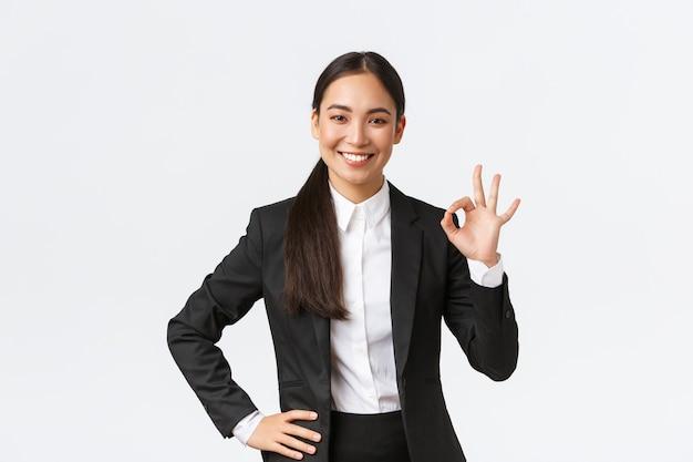Professionele vrouwelijke manager in een zwart pak die er assertief uitziet, alles goed aanmoedigt, het werk verzekert, een goed gebaar toont en goedkeurend glimlacht, tevreden over een witte achtergrond