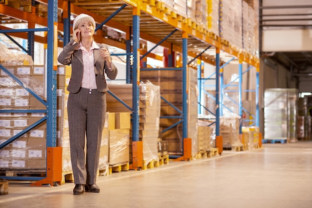 Professionele vrouwelijke manager praten aan de telefoon tijdens het bespreken van de werkkwesties